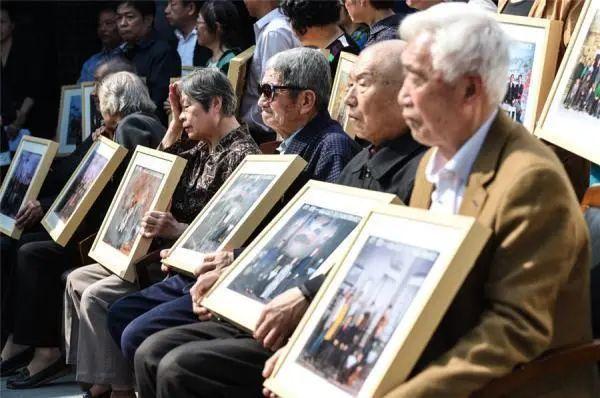 南京大屠杀幸存者傅兆增(前排右二)等与部分幸存者家属代表在开幕式上展示家族合影