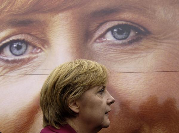 2005年9月10日,德国普雷罗,德国总理候选人默克尔从自己的海报前走过。