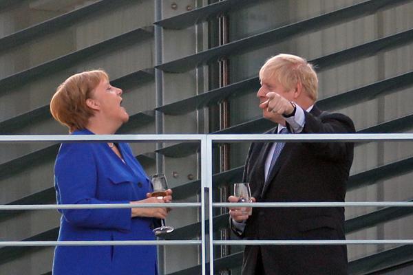 当地时间2019年8月21日,德国柏林,德国总理默克尔与来访的英国首相约翰逊在总理府的阳台上喝酒。英国首相约翰逊日前要求欧盟重启英国脱欧协议的谈判,于21日和22日两日先后访问德国和法国,争取两国领导人支持。