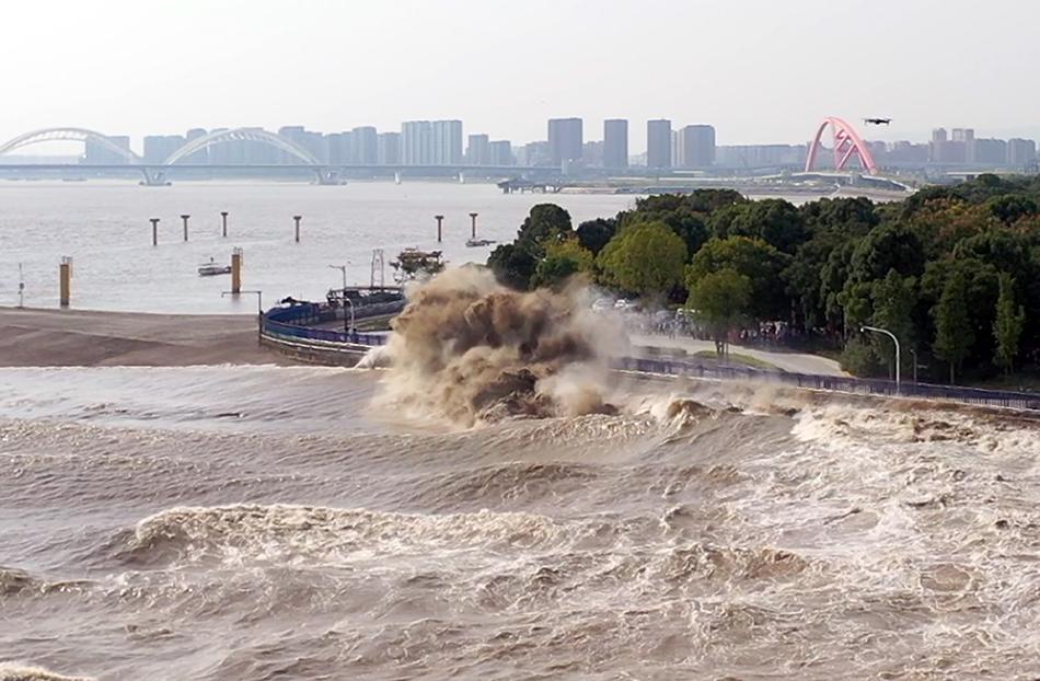 在杭州下沙江堤上,众多市民和游客争睹钱江大潮的壮观景象。