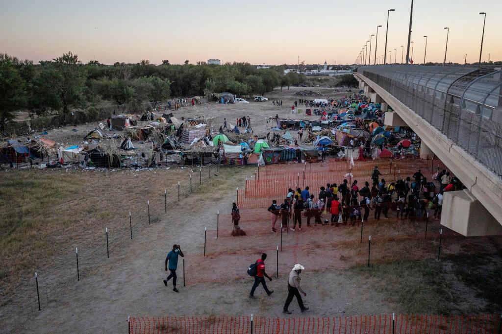 """当地时间2021年9月23日,美国得州,美墨边境""""德尔里奥跨国大桥""""下的临时营地被清理,非法移民排队离开。"""