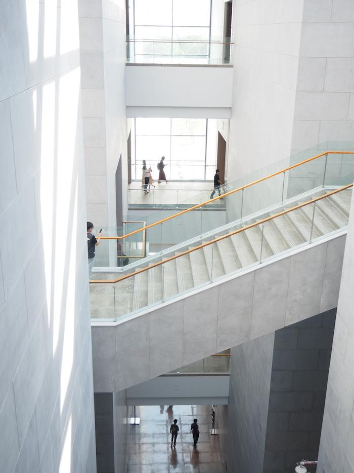 建筑间采用透明玻璃贯通衔接,阳光透过玻璃洒下斑斑驳驳的光影。