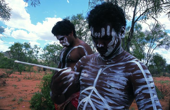 在跳舞前涂绘油彩的原住民青年(2000年2月于澳洲中部爱利斯泉附近沙漠边缘地区,李公明摄)