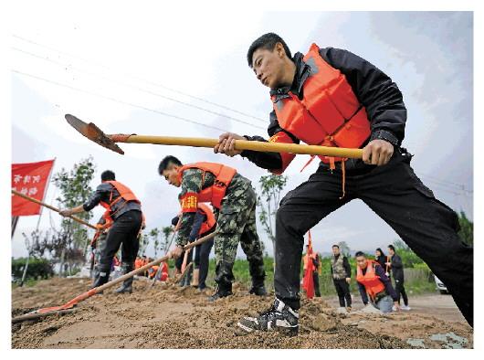 10月10日,抢险人员在连伯村加固临时堤坝。新华社记者 詹彦 图