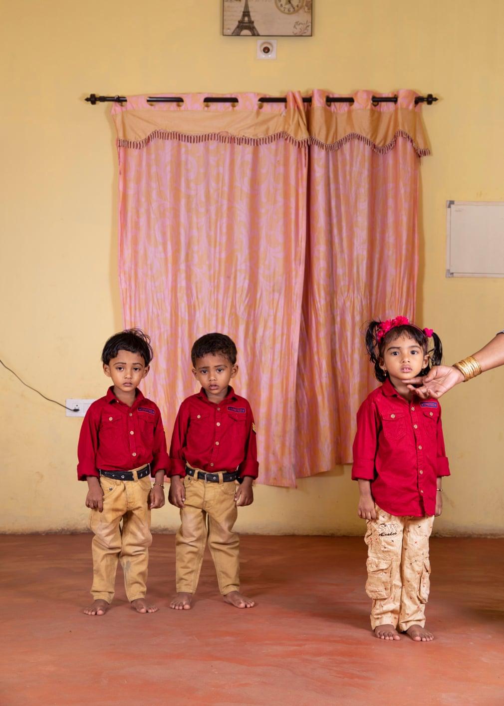 """三胞胎穿着一件绣有""""团结""""字样的衬衫,但他们的未来将截然不同。许多印度人与大家庭住在一起;婚后,男孩们将留在家里。而母亲抬起女儿的下巴,让她面对自己的命运。结婚后,女孩将与公婆同住。戴一套手镯的母亲,是已婚妇女的标志。"""