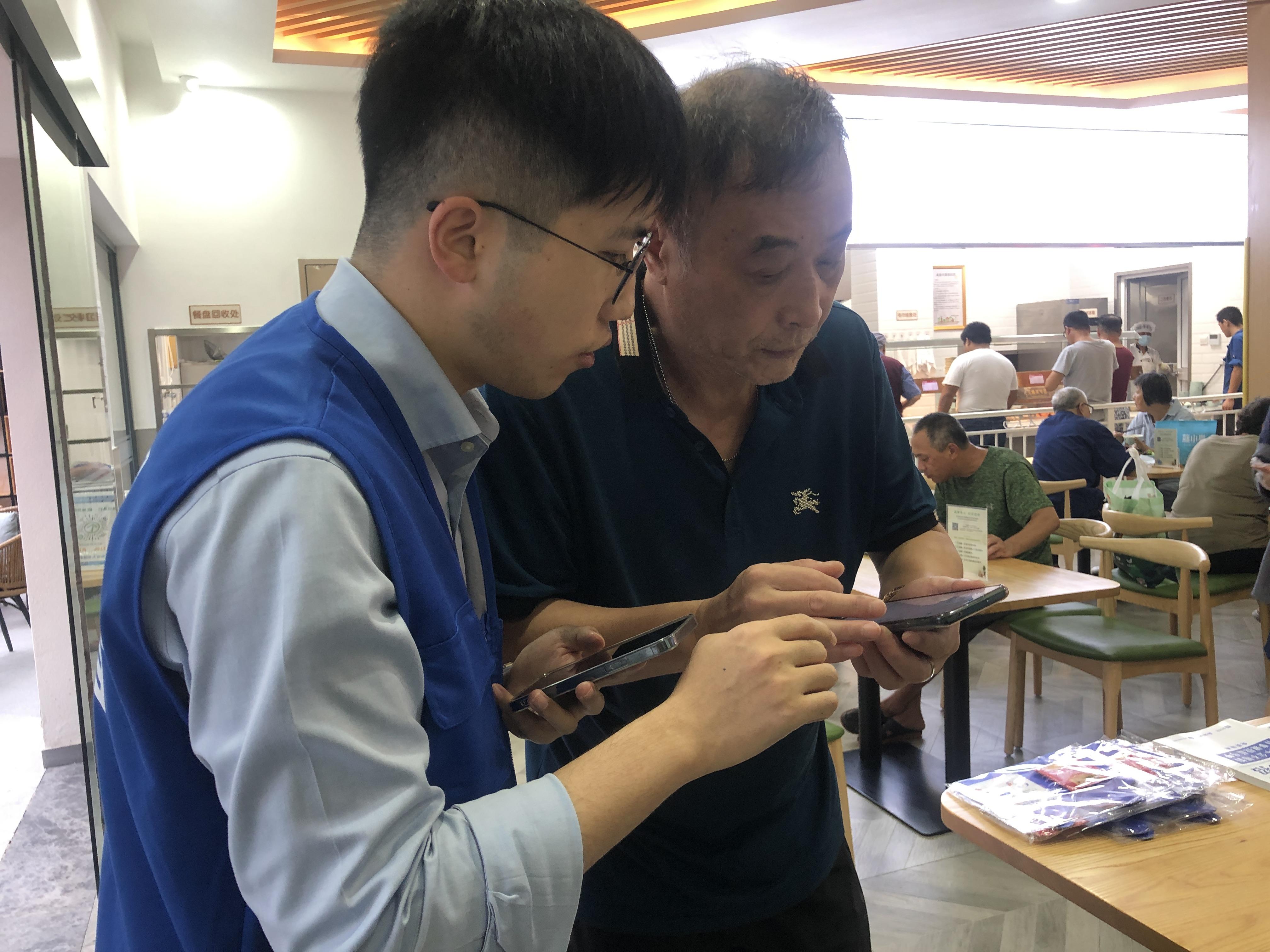 蓝马甲志愿者教社区老人用智能手机。