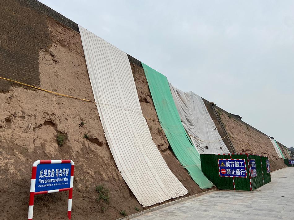 在城墙上覆盖塑料布是平遥古城墙防垮塌的措施之一。