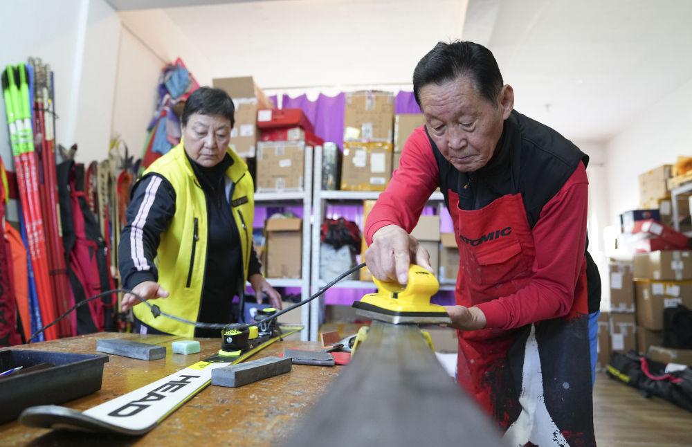 10月12日,朴东锡(右)、张桂珍帮助雪友保养雪板。新华社记者许畅摄
