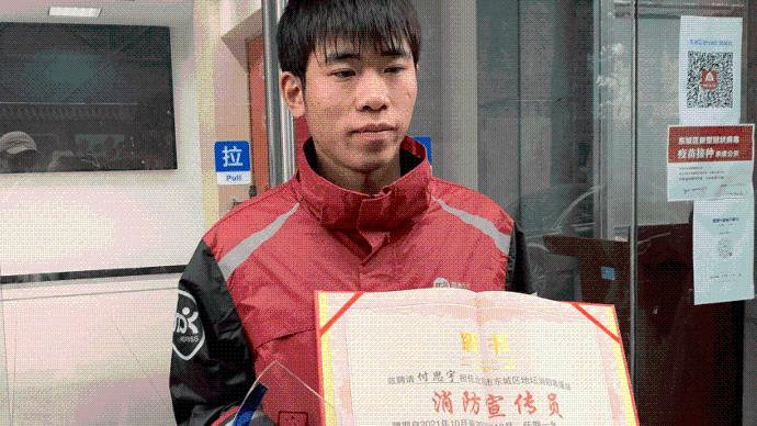 雨中为消防车疏导交通,北京一快递小哥被授荣誉奖杯