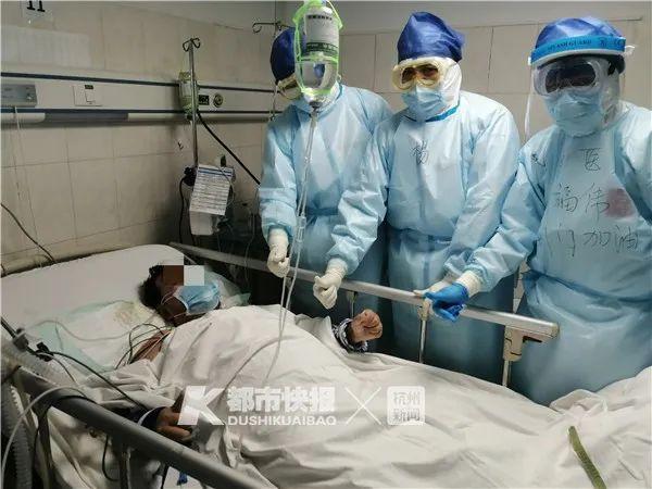 荆门首例ECMO患者成功撤掉呼吸机,在病床上竖起大拇指,和医护人员合影。