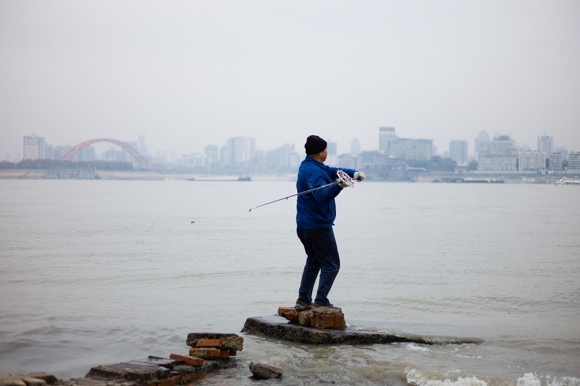 2015年,谌毅在武昌江边拍摄的钓鱼人,远景是汉江口。