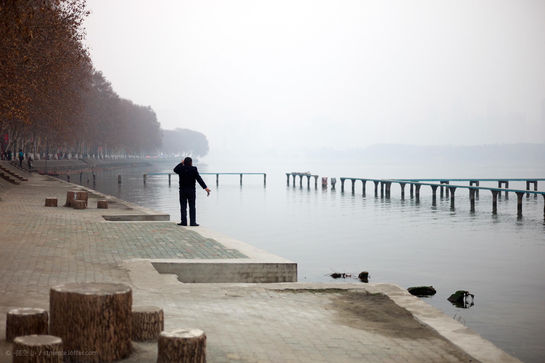 一位男士正在用东湖水洗脸,谌毅拍摄于武汉大学凌波门外。