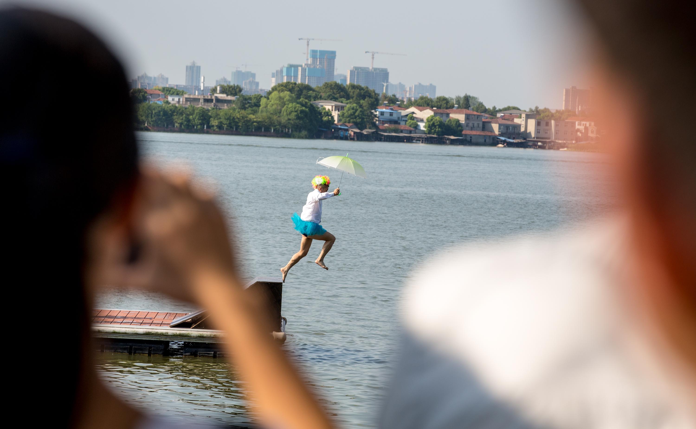 """2018年8月25日,""""跳东湖""""活动在武汉东湖磨山楚城水上栈道举行,参与者现场报名,穿上救生衣,以各种姿态体验花样跳东湖。 张畅 摄 中新社 图"""