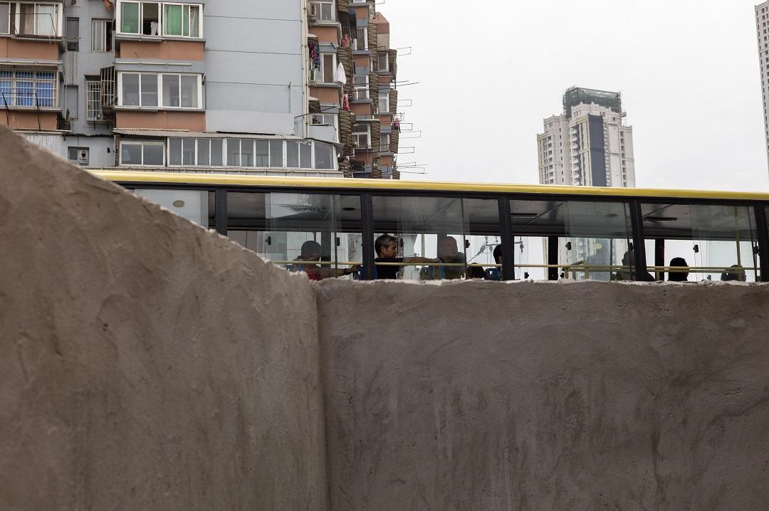 2015年,谌毅在汉阳古城西大街拍摄的驶过拆迁围挡的双层巴士。