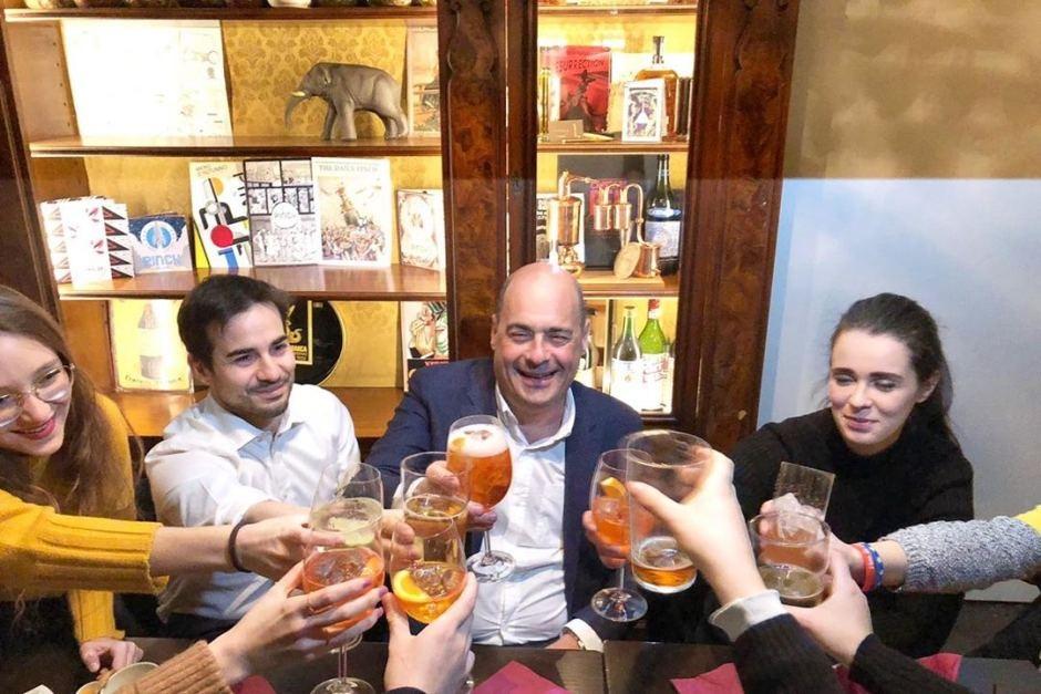津加雷蒂在酒吧和学生举杯共饮。