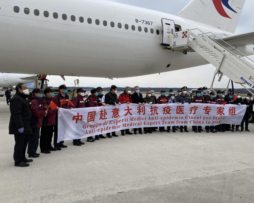 3月25日,在意大利米蘭馬爾奔薩機場,中國第三批赴意大利抗疫醫療專家組成員與意方人員合影。