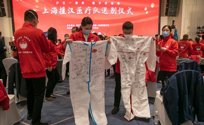 3月30日,送别仪式上,上海首批援汉医疗队的队员们展示签满姓名的防护服。