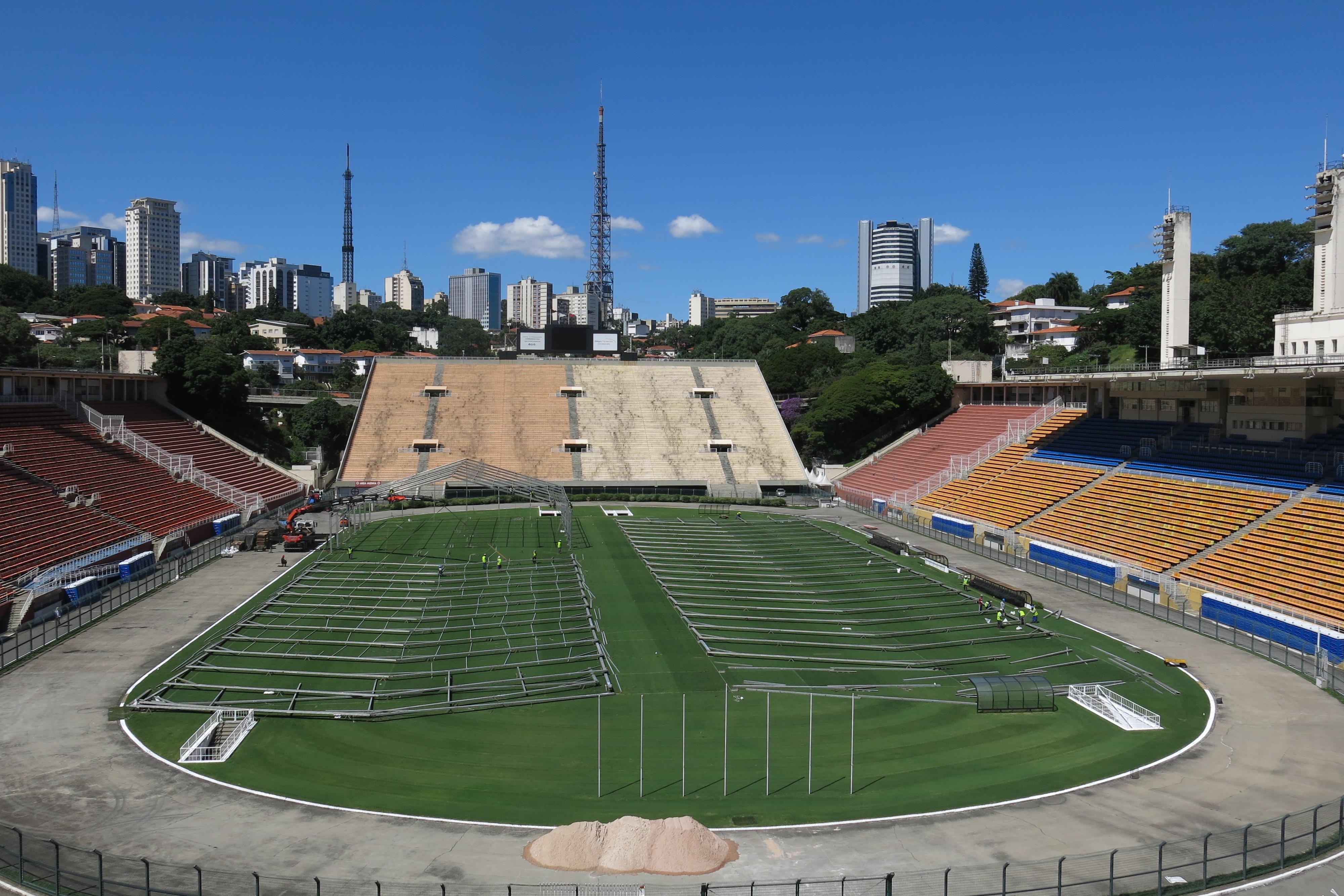 """3月23日,修建工人在巴西圣保罗市的帕卡恩布体育场内建造""""方舱医院""""。新华社 图"""