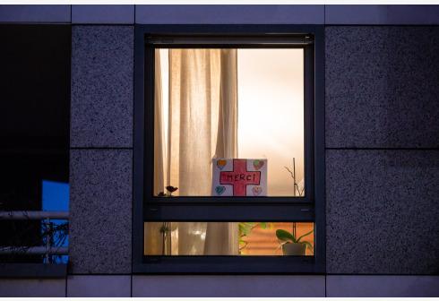 """3月25日,在法国巴黎,一户人家在窗台上摆放着自制标语,上面写着""""谢谢""""。 新华社 图"""