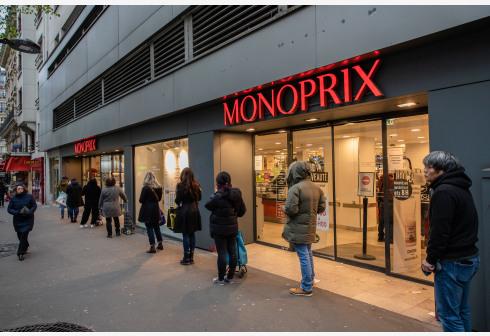 3月21日,在法国巴黎,人们在一家超市外保持间距排队。 新华社 图