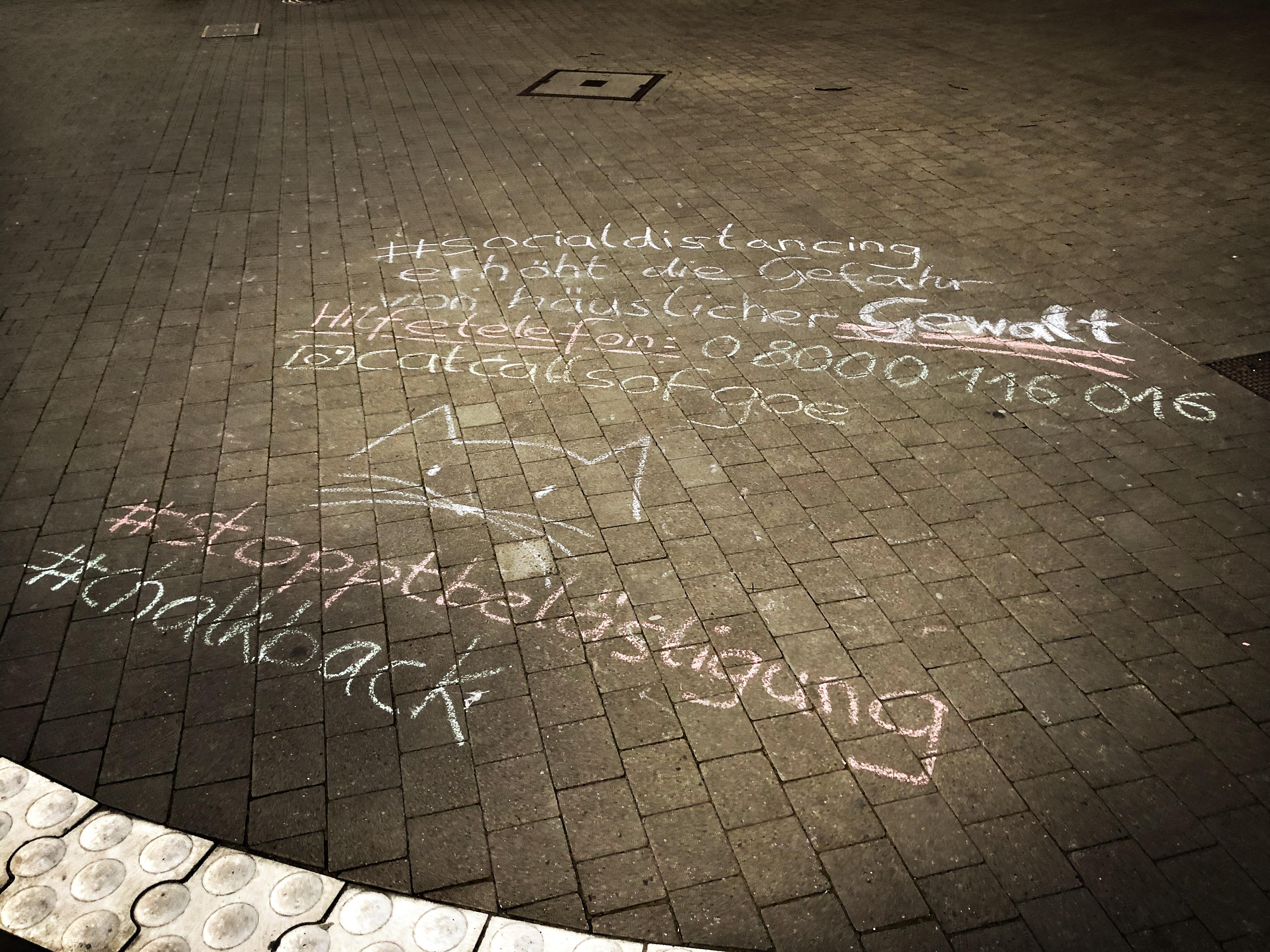 地面的涂鸦:社交距离会使家庭暴力的危险升高,有必要可拨打援助电话。