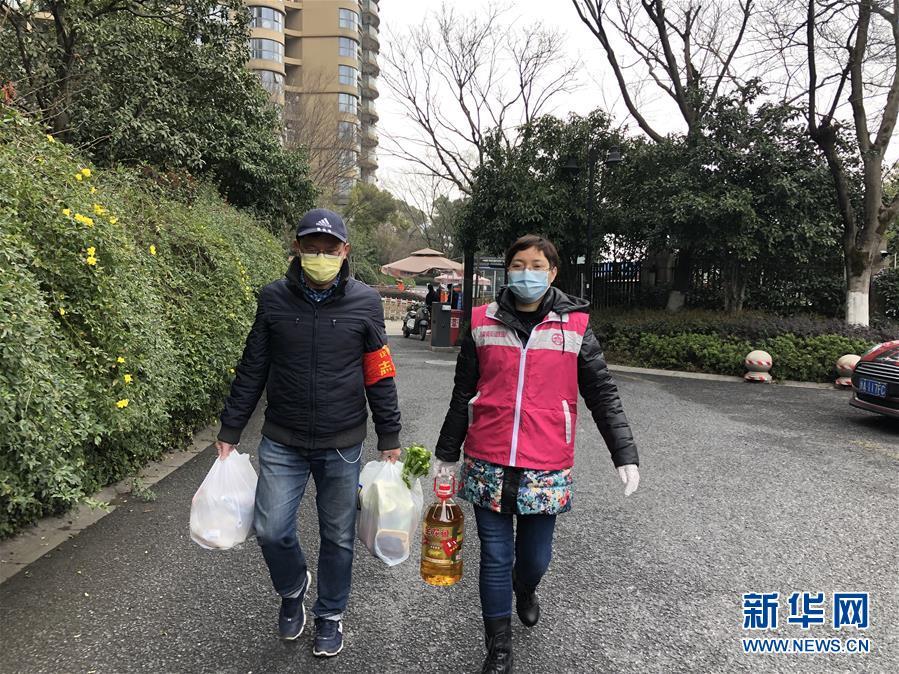 杭州市四季青街道錢塘社區工作人員和志愿者給隔離戶送生活物資(3月2日攝)。新華社 發