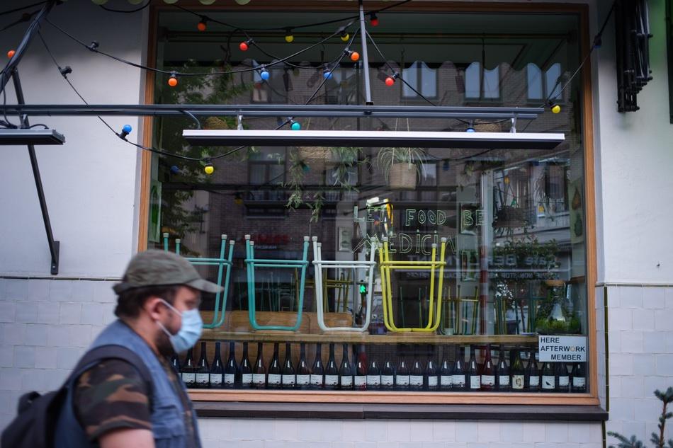 4月17日,在比利时布鲁塞尔,一名戴口罩的男子经过一家关闭的餐馆。 新华社 图