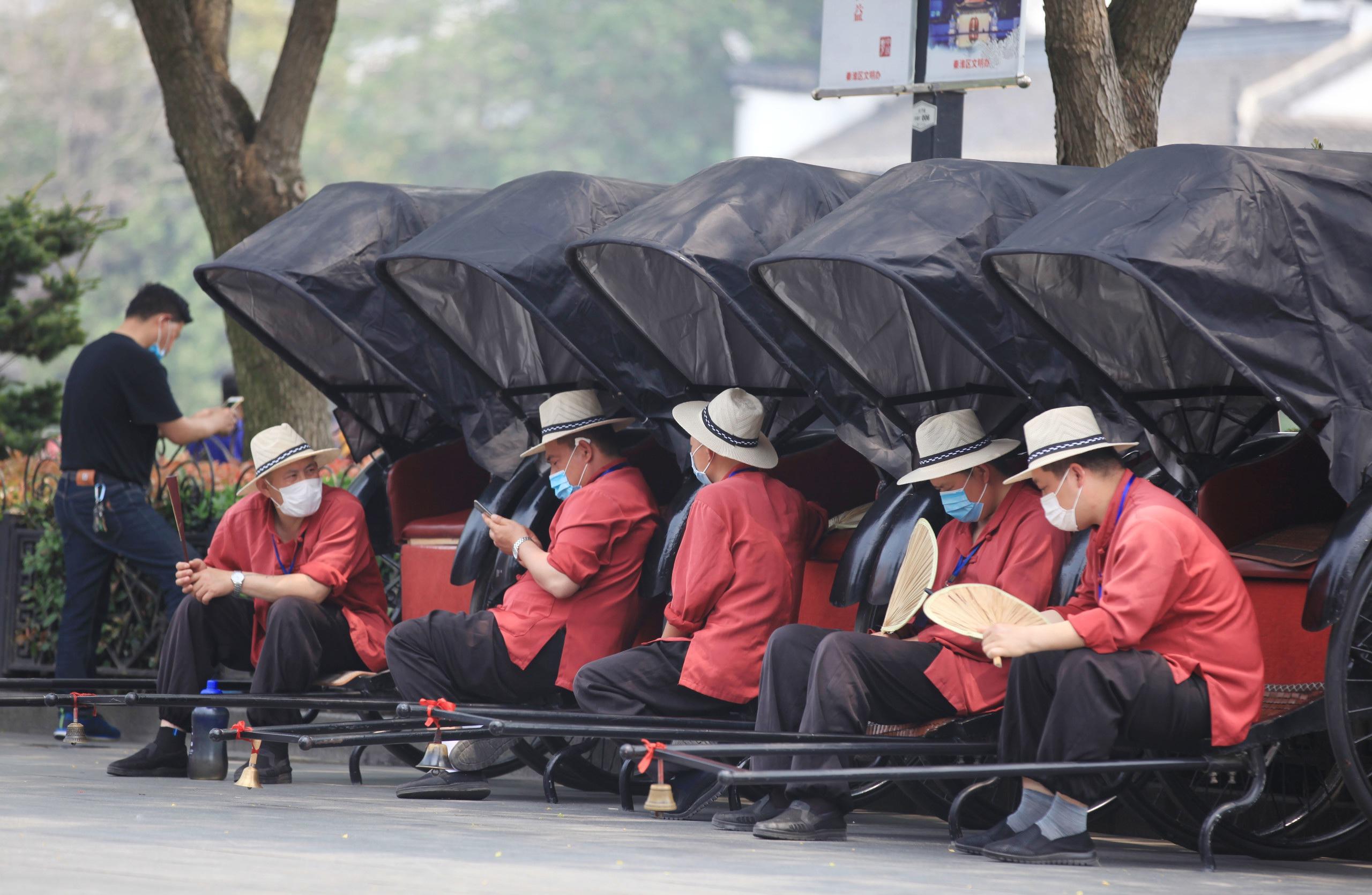 2020年5月4日,南京市变态高温,在夫子庙景区,拉黄包车的师傅都戴着遮阳帽期待游客。IC photo 图