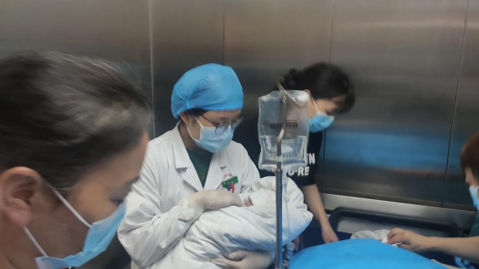 湖北省婦幼保健院婦產科大樓,醫護人員抱著彭銀華的新生女兒。 澎湃新聞記者 鄭朝淵? 圖