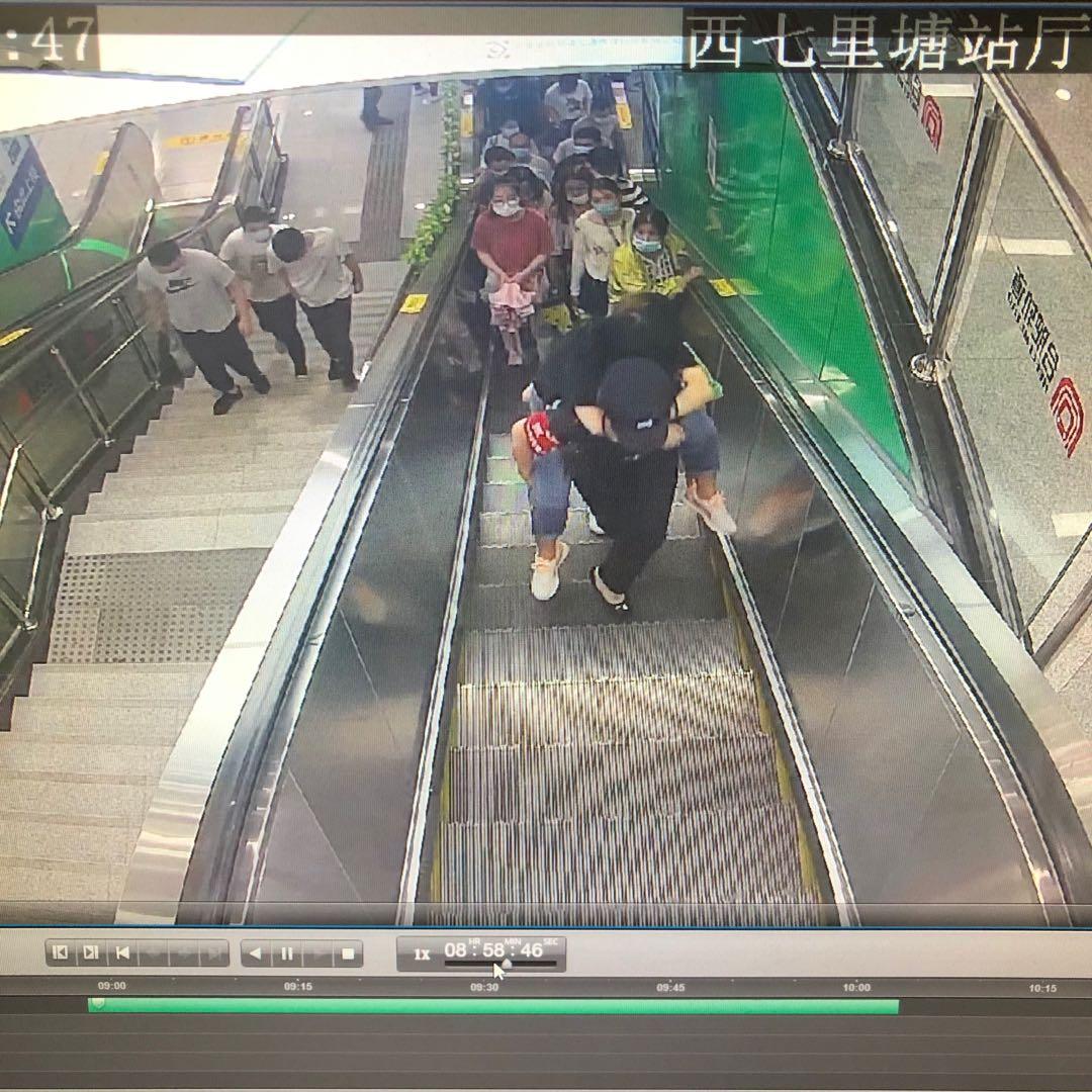 陈春惠背起女乘客一边乘扶手电梯,还一边向上走。