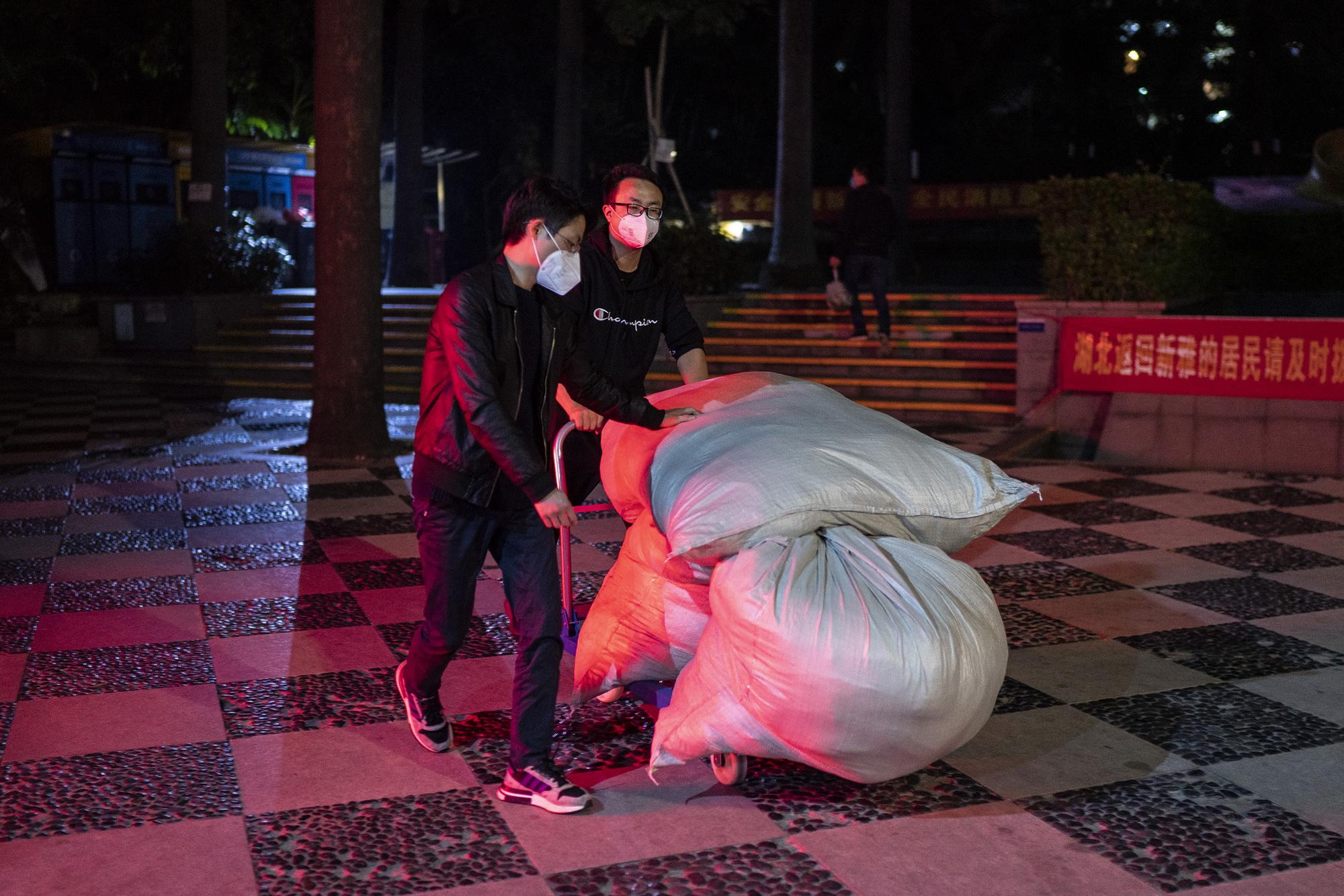 2020年2月20日,王体能和江帆戴上口罩,拉着小推车,把包裹送上物流车。