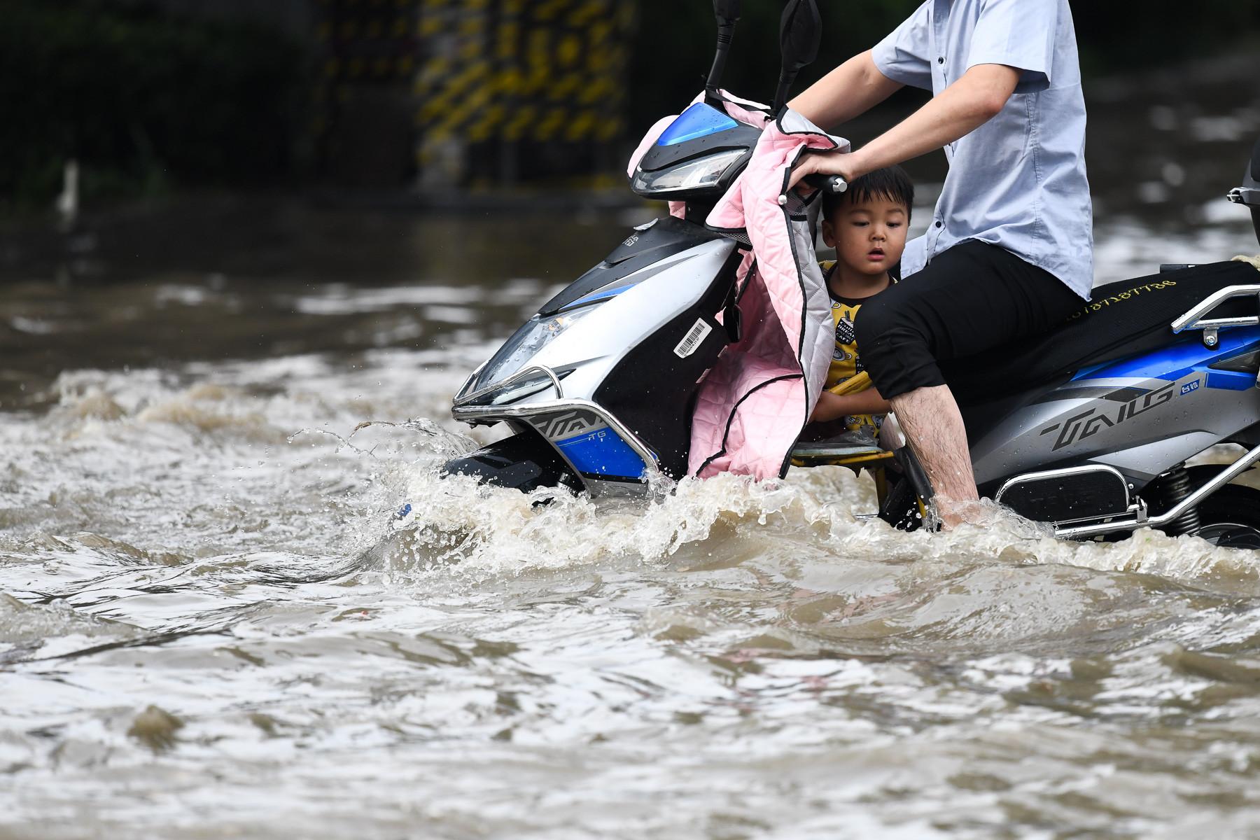 """7月4日,河南省鄭州市,一場突如其來的暴雨,讓路成""""海""""。由于積水較深,有人騎電動車通過,有人抱著孩子走過去,還有被朋友背過去…… IC 圖"""