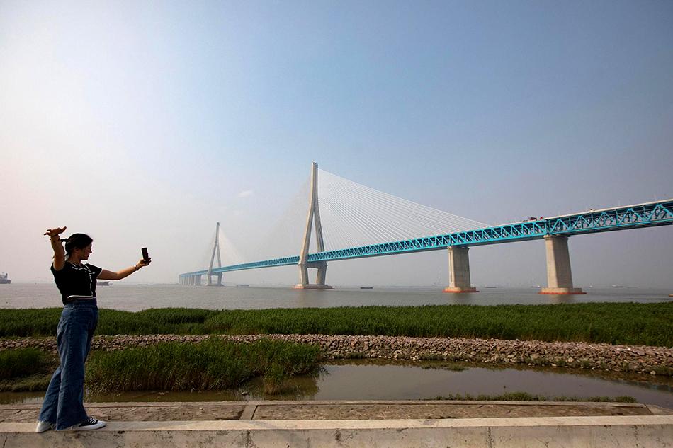 6月30日,一名女子在滬蘇通長江公鐵大橋南岸拍照。該橋于7月1日正式通車。橫跨長江,兩岸連接江蘇省南通市和張家港市,為國內最大跨度斜拉橋,也是世界最大跨度公鐵兩用斜拉橋。泱波/中新社 圖