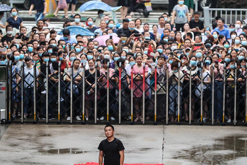 7月5日,安徽,合肥六中,離校的學生走到校門口后,回頭望向教學樓。當日,合肥六中高三學生上完最后一課,離開學校,即將迎戰高考。人民視覺 圖