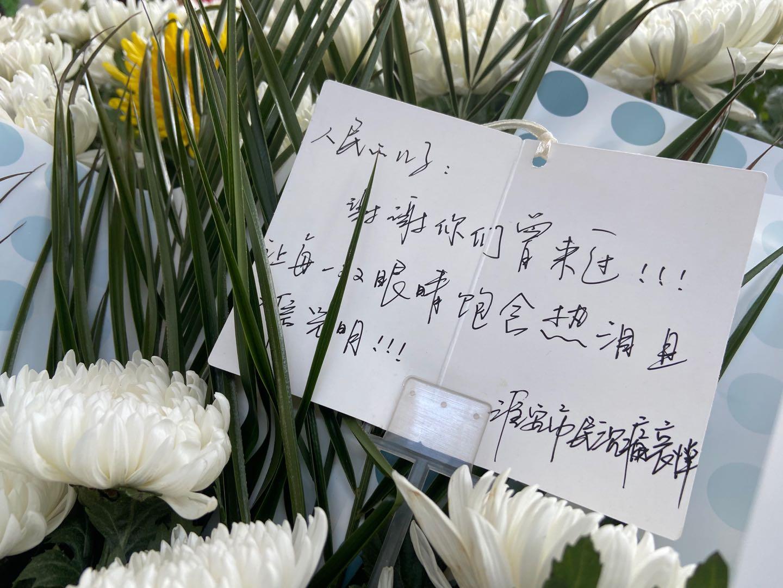 """一名淮安市民送别两人,献上的鲜花中有一张卡片,写到:""""谢谢你们曾经来过,让每一双眼睛饱含热泪且相信光明。"""""""