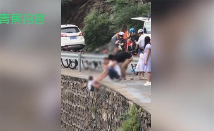 视频丨网曝北京房山有家长把孩子挂峭壁拍照,无任何防护措施
