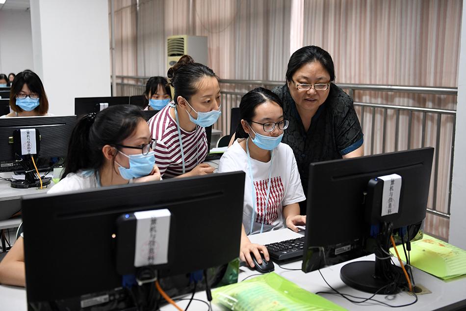 2020年7月12日,重庆市高考阅卷有序进行。在西南大学高考评卷现场,教师们在进行探讨。 新华社记者 唐奕 摄