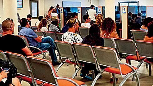 图为等待领取失业救济金的以色列民众