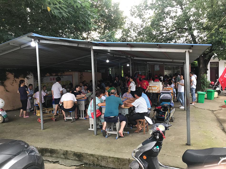 受灾群众聚集在桥头小学安置点大棚下,准备吃饭。