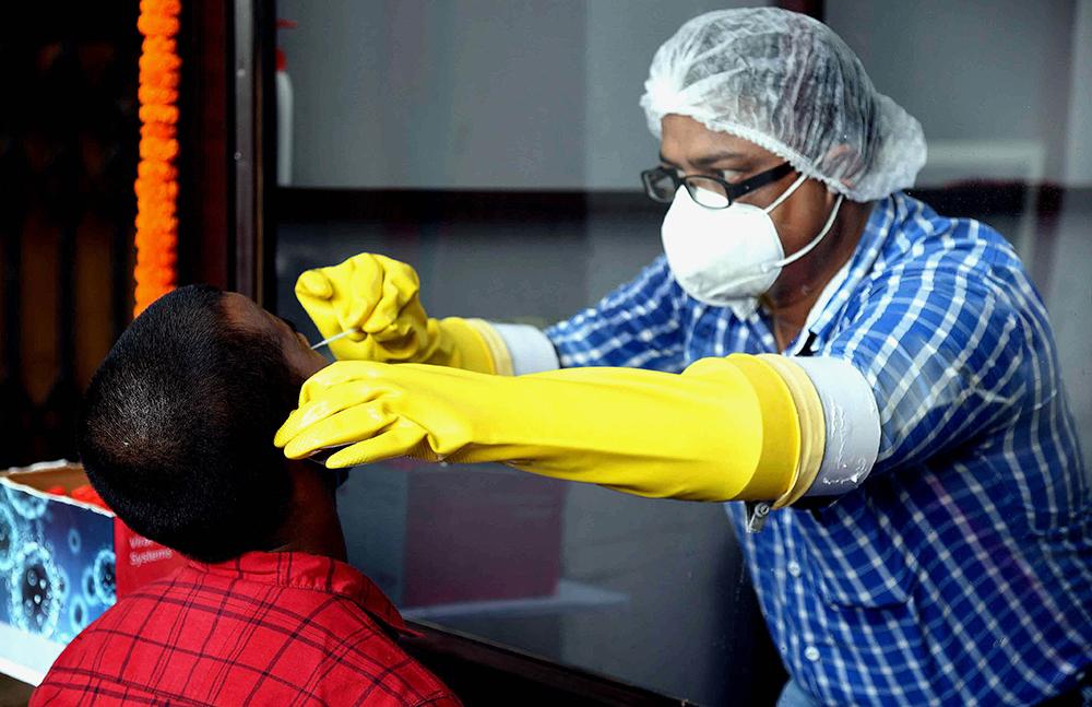 7月14日,一名医务人员(右)在印度巴特那为居民进行新冠病毒检测取样。 新华社 图