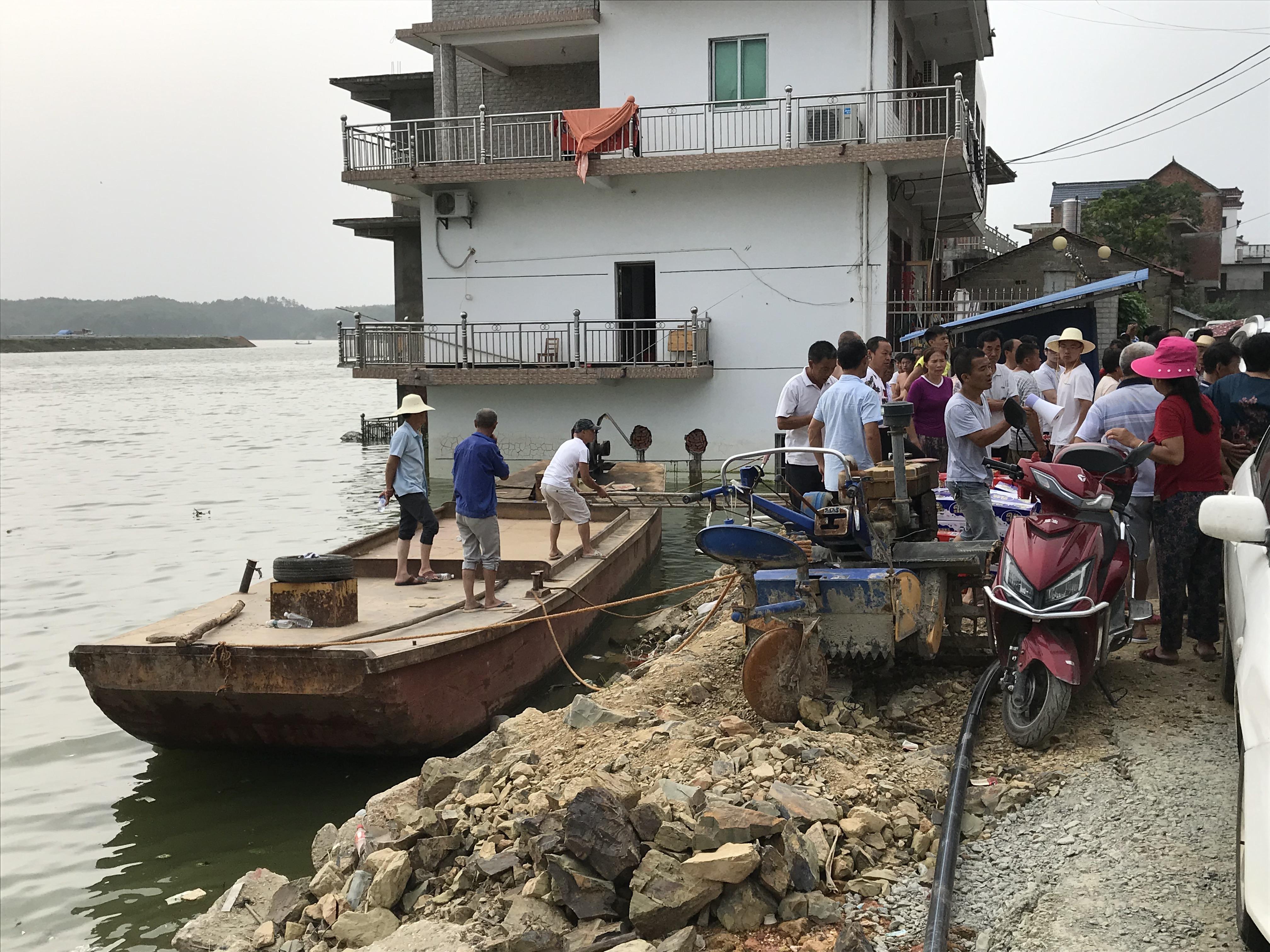 由于决堤导致道路中断,捐助给村民的物资只能通过船运。