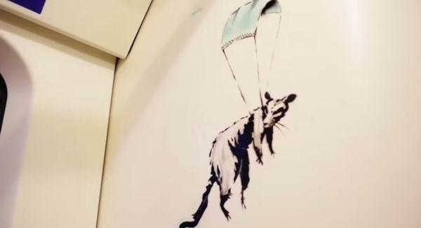 伦敦地铁车厢中,班克斯画下的以口罩做降落伞的老鼠。