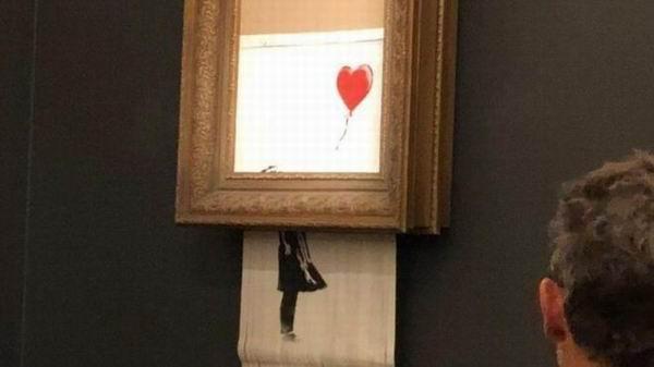 """班克斯作品""""手持气球的女孩""""在拍卖成交后旋即""""自毁"""" 。"""