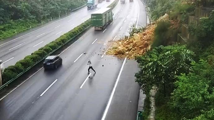 暖闻|山体滑坡致公路被阻,民警不顾危险路中挥手示意车辆