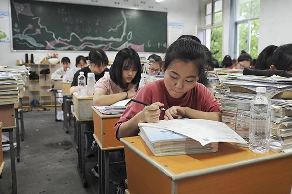 2020年7月7日,安徽黄山歙县二中高三考生在教室内复习功课。因暴雨导致歙县城区积水严重,原定于当日举行的高考语文、数学两科考试延期举行。