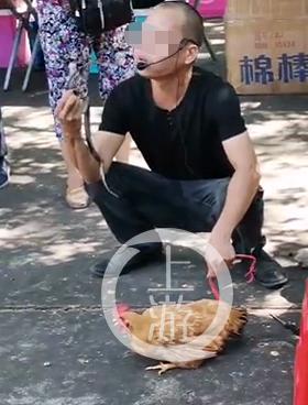 7月29日,广西来宾市兴宾区平阳镇,当地群众拍下该男子摆摊卖蛇酒的情形。 视频截图