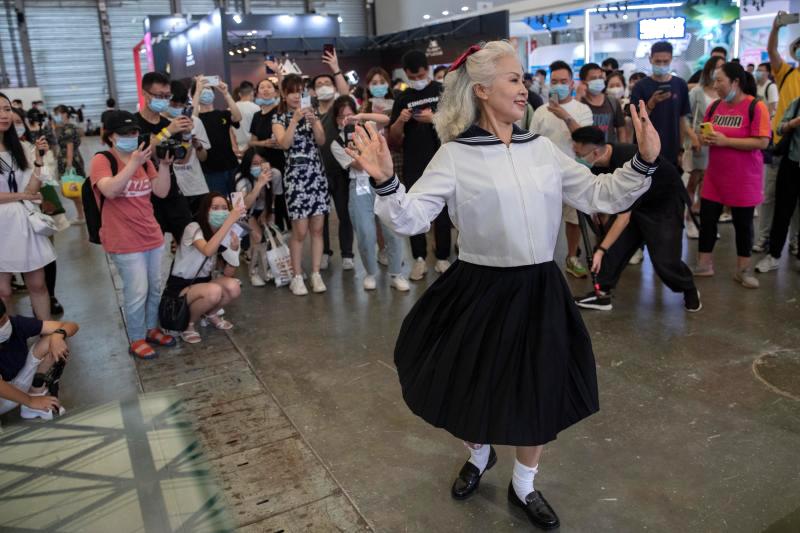 """7月31日,2020ChinaJoy在上海新国际博览中心开幕。闲鱼展区前,一头扎着蝴蝶结的白发,身穿女高中生(JK)制服,66岁的高建华奶奶正在跳二次元宅舞,她是整个现场年纪最大的Show girl。高奶奶也是目前网上爆红的""""时尚奶奶团""""成员之一,社交平台上粉丝超过了500万。赖鑫琳/上观新闻 图"""