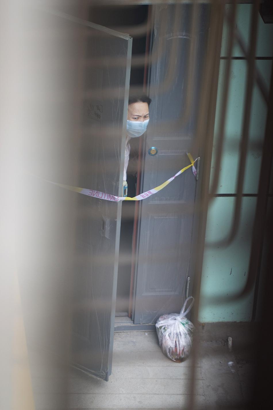 7月29日,乌鲁木齐市疫情防控措施依然严格,一个小区的单元门被拉上了隔离带,小区居民积极配合,封闭在家。买菜由志愿者送上门,倒垃圾也是服务到家。任春山/人民视觉 图