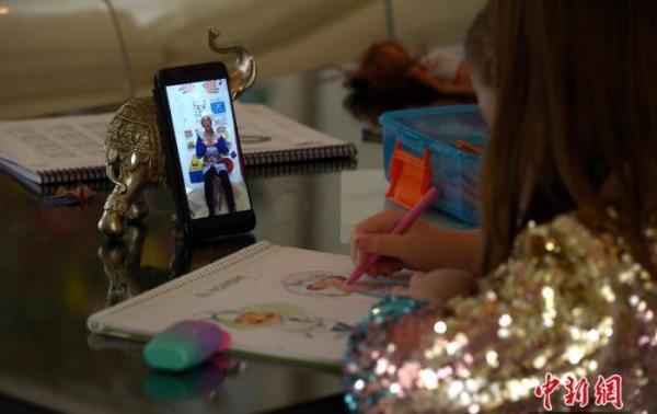 在西班牙,一名小女孩正在自己的网课时间。 中新网 图
