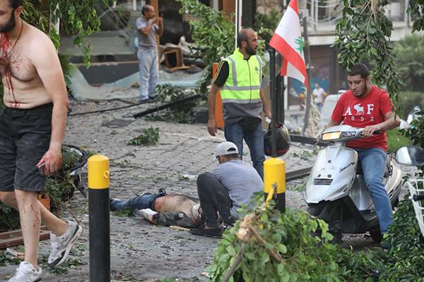 8月4日,在黎巴嫩首都贝鲁特,人们救治一名爆炸中的伤者。新华社 图
